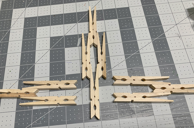Clothespins-laid-out-on-a-cutting-mat-to-form-a-cross