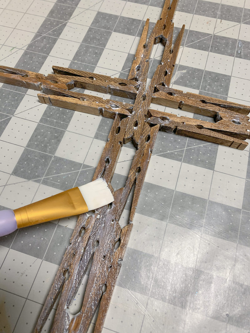 Sealing-a-DIY-clothespin-cross-with-Mod-Podge