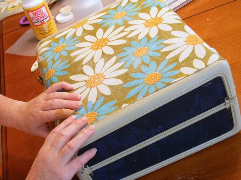 Smoothing fabric on the top of a suitcase