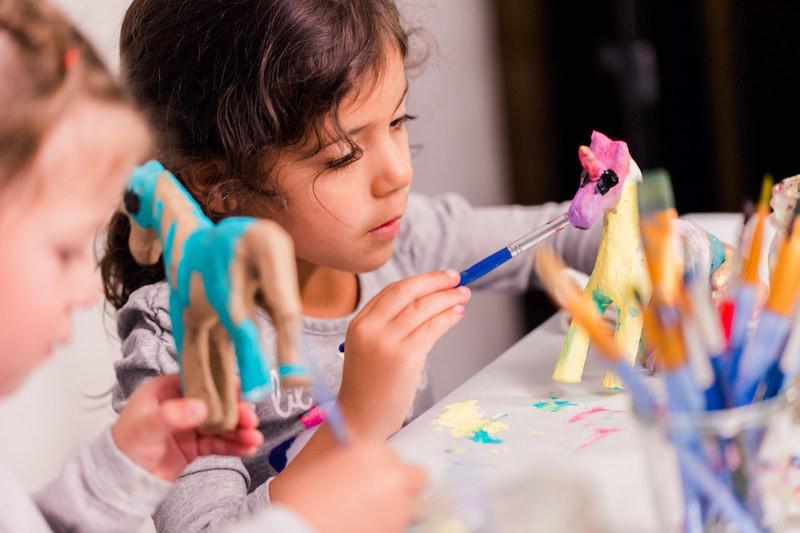 Child painting a paper mache unicorn