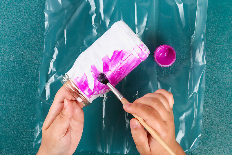 Hands painting a white mason jar with pink paint