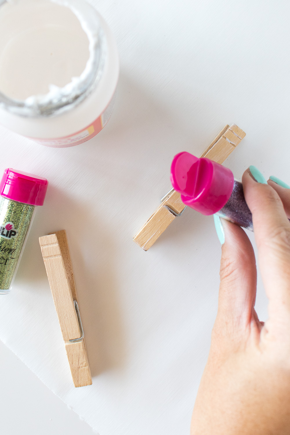 sprinkling glitter on the top of clothespins