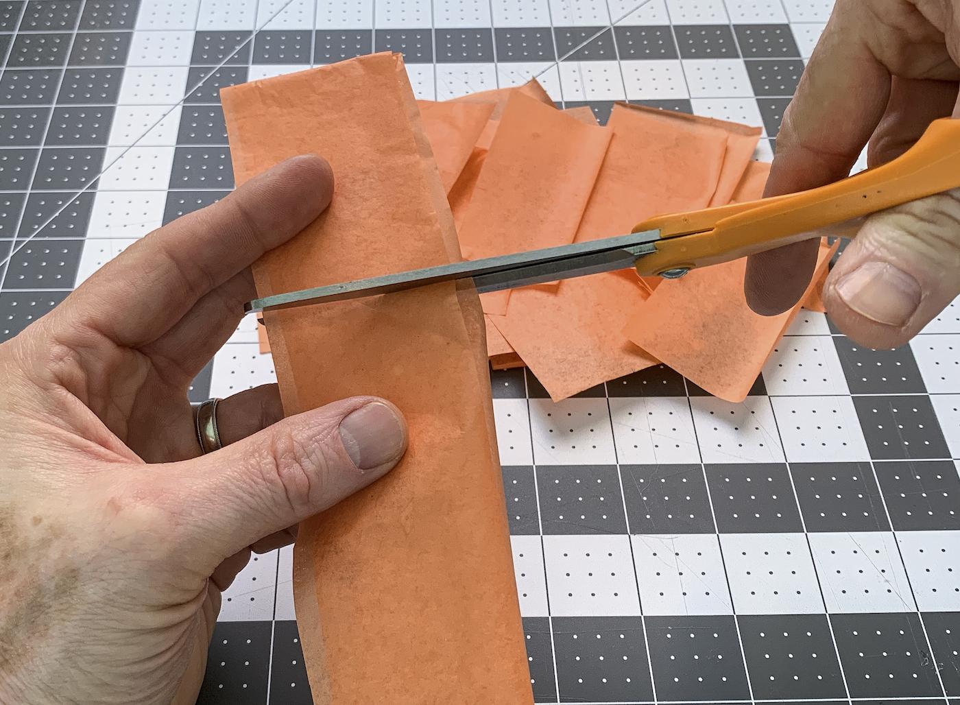 Corte de papel de seda em quadrados com uma tesoura