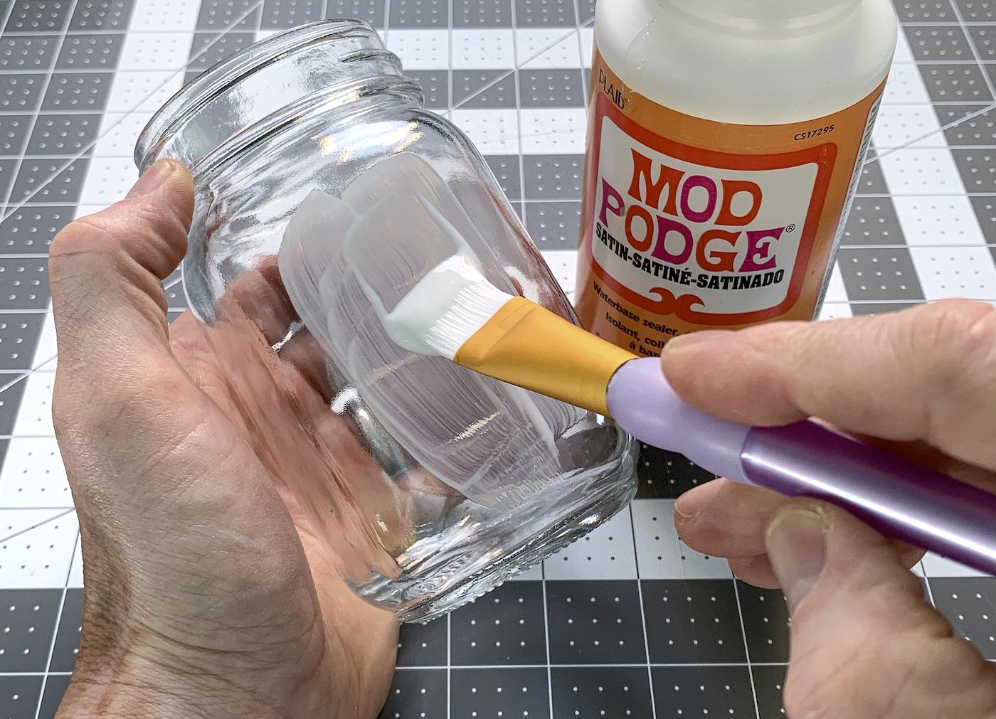 Pintando Mod Podge do lado de fora de um frasco de vidro com um pincel