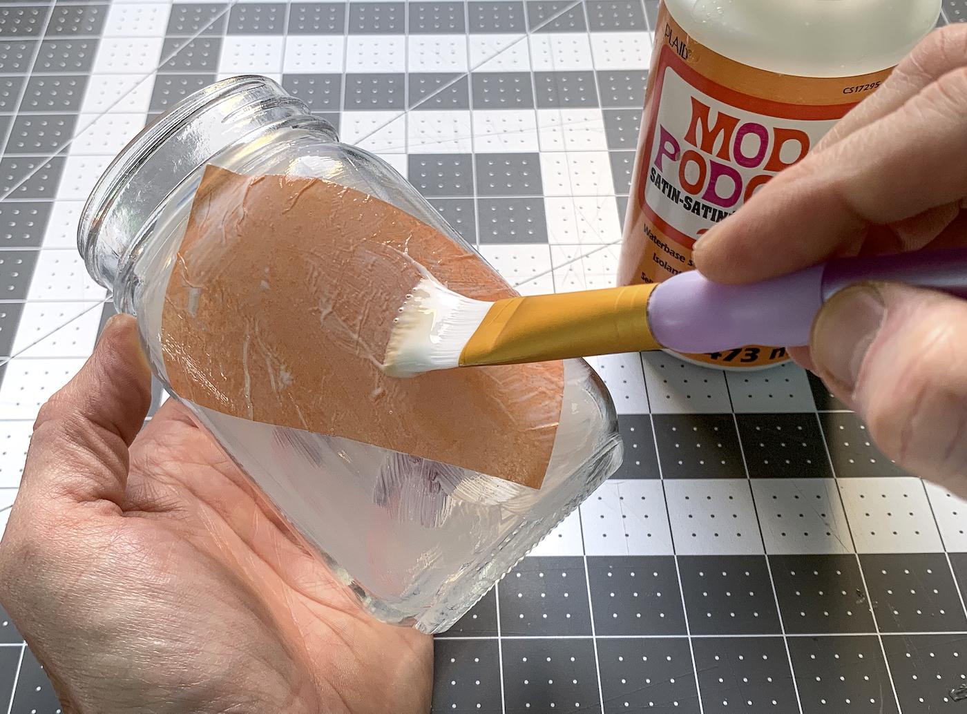 Pintando Mod Podge em cima de um pedaço de papel de seda laranja com um pincel