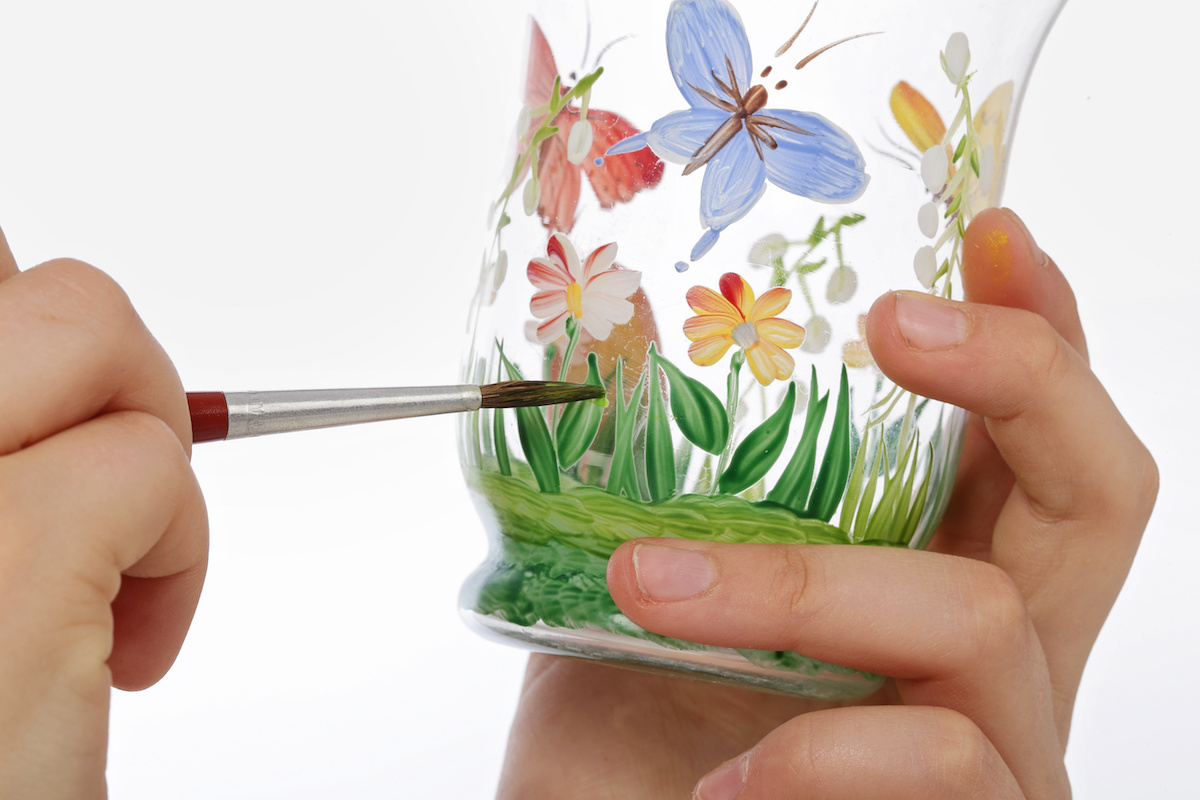 Painting-grass-and-butterflies-on-glass-with-a-paintbrush
