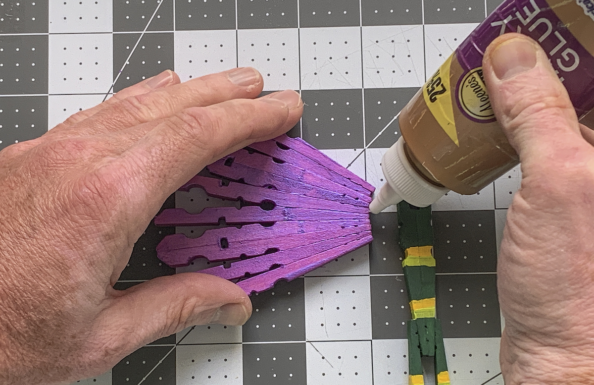 Adding craft glue to a purple dragonfly wing