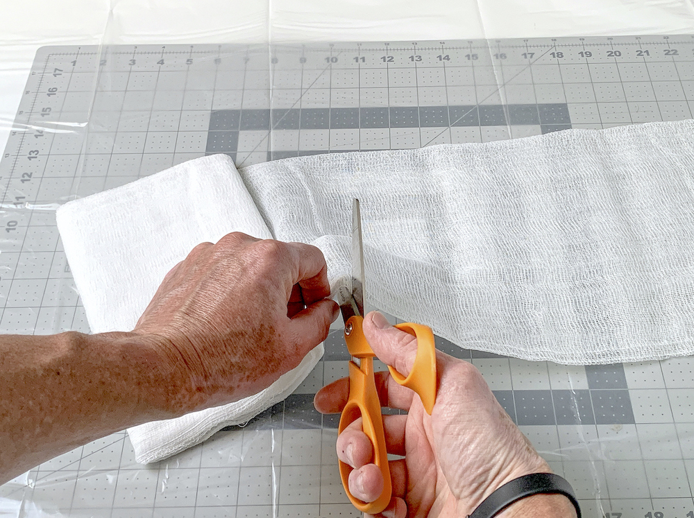 Cutting cheesecloth with a pair of scissors