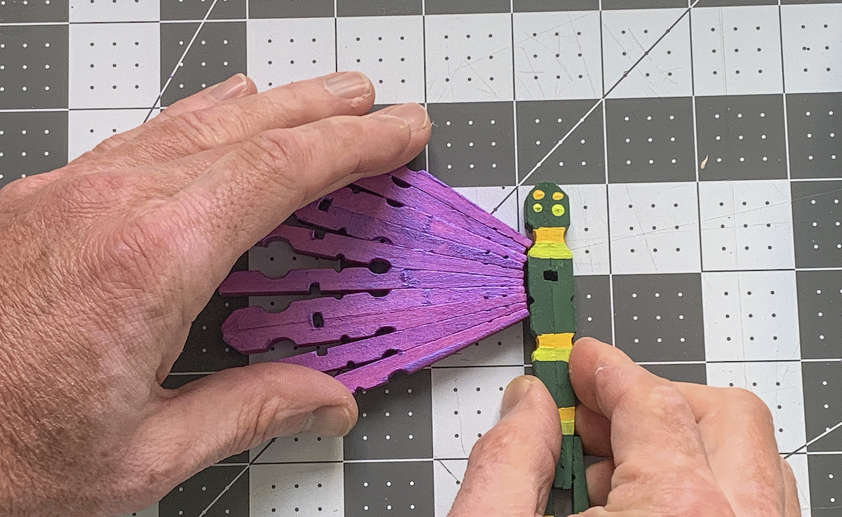 Gluing a clothespin wing onto the dragonfly body