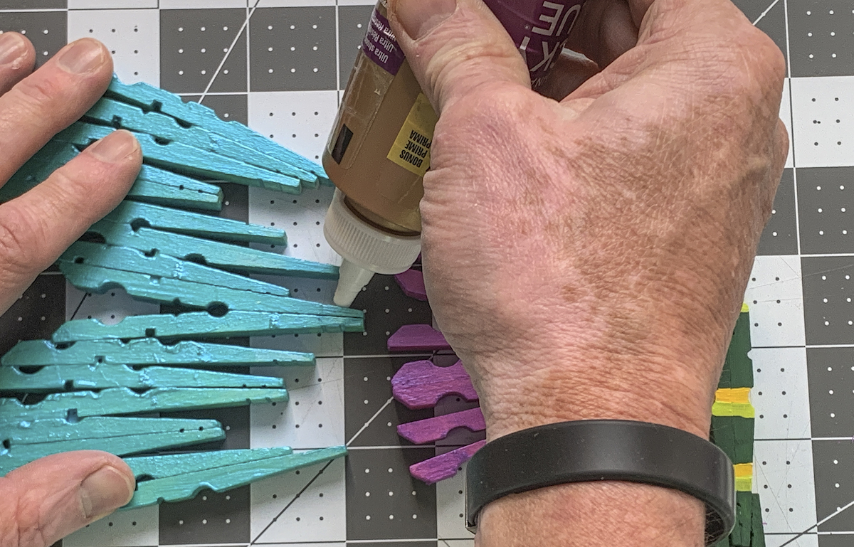Gluing the wings of the clothespin dragonflies