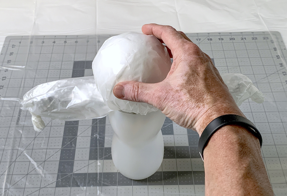 Hand placing a ball on top of the ghost mold