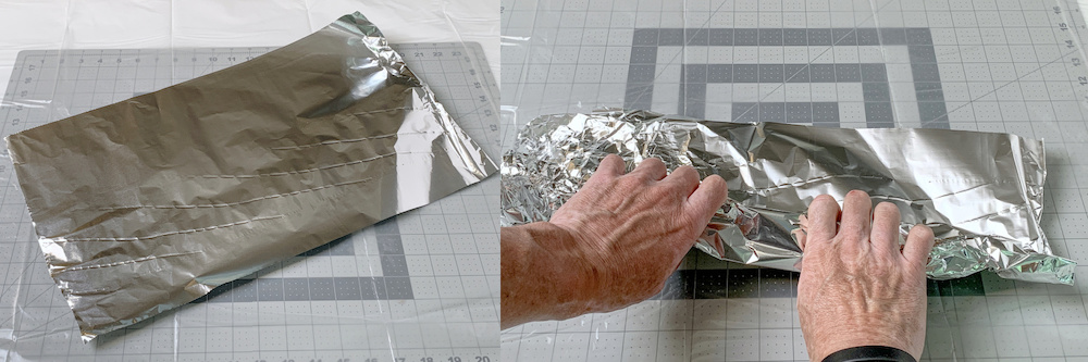 Hands rolling aluminum foil into a tight roll