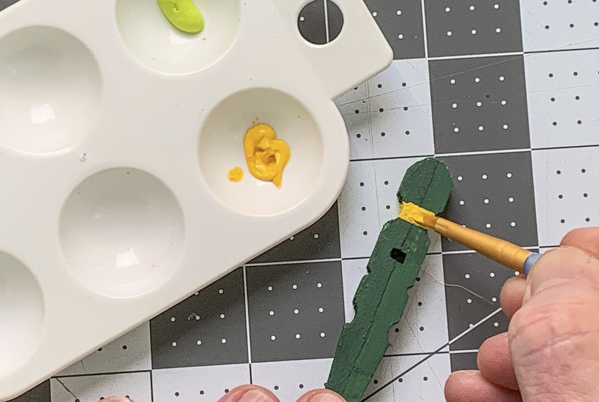 Painting clothespins with yellow craft paint