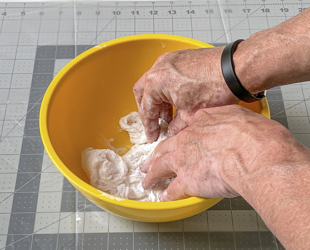 Two hands pressing cheesecloth into the fabric stiffener in a bowl
